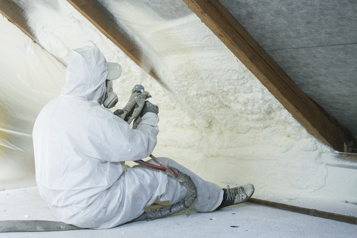 A worker spraying attic insulation to reduce overall home energy usage